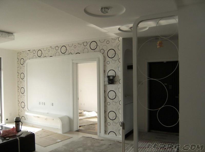 电视背景墙隐形门:电视背景墙处设置了一个装饰条,而这里是个隐藏的门,打开之后是另一个空间,这个门既有装饰效果,同时又起到分割的作用。  电视背景墙隐形门:如果你的家的布局类似图片上所显现?#21738;?#26679;,卧室或者卫生间的门和电视背景墙恰好在一面,看上去窄窄的背景墙处难以做出什么新的造型了,但是如果用钢化的隐藏门作为电视背景墙的装饰块,不仅节约了空间,而且整体和谐感凸?#28020;? 电视背景墙隐形门:在背景墙的处理上,设计师首先是把次卧的门设计成了隐形门,没有门框,和背景墙保持统一平面,窗户、背景墙、次卧门部分都采用白色底